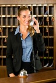 17798549-reception-of-hotel-desk-clerk-woman-taking-a-call-and-smiling.jpg