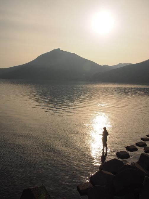 夕時の支笏湖畔と釣り人