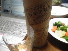 [写真]ダイニングテーブル上の大麦焼酎・百年の孤独とグラスとパソコン