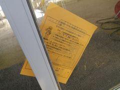 [写真]受付ハウスのドアに挟まれたパトロール連絡カード